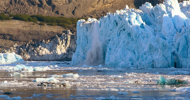An iceberg calves off of Yahtse Glacier into Icy Bay.  Timothy Bartholomaus