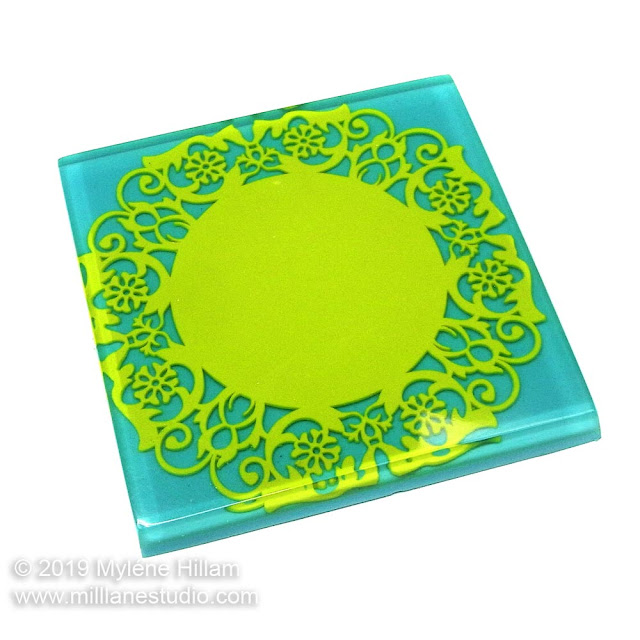 Square turquoise resin coaster embedded with green doiley