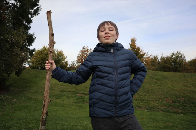 Boy holding stick wearing Reima Falk Winter Jacket