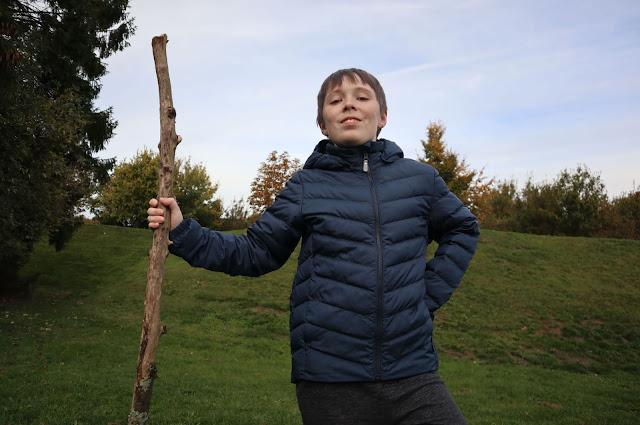 Boy holding stick wearing Reima Falk Winter Jacket