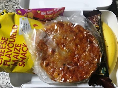 Lunch box with pizza, maize snack, banana and chocolate