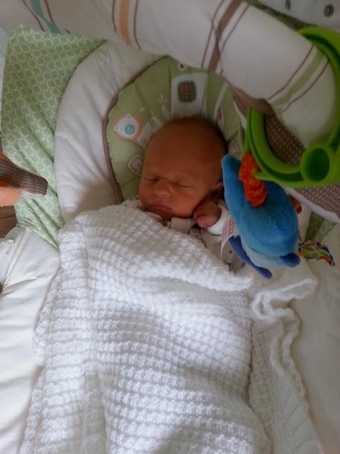 A newborn baby sleeping in a baby glider