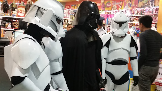 Three Jedi cosplayers in front of a shop