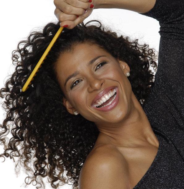Mulher penteando cabelos cacheados e sorrindo