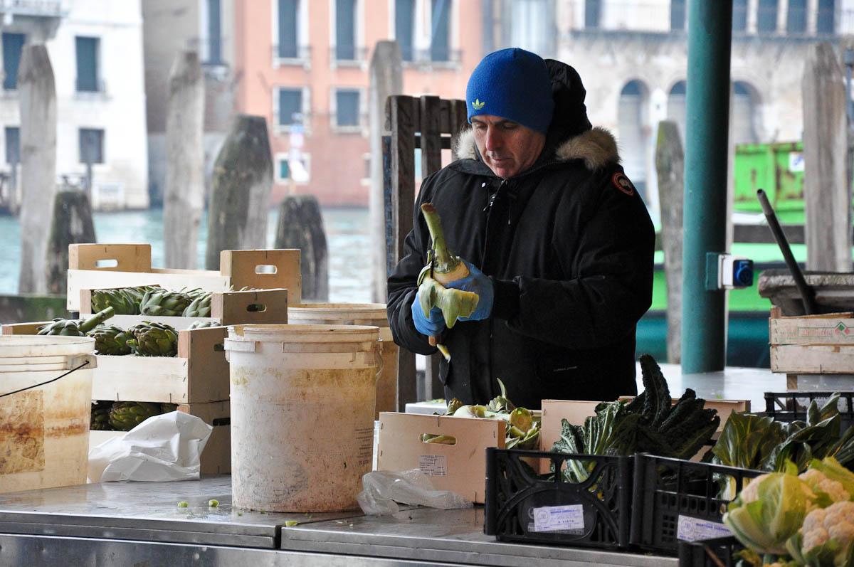 A market trader cuts out artichoke hearts, Rialto Market, Venice, Italy