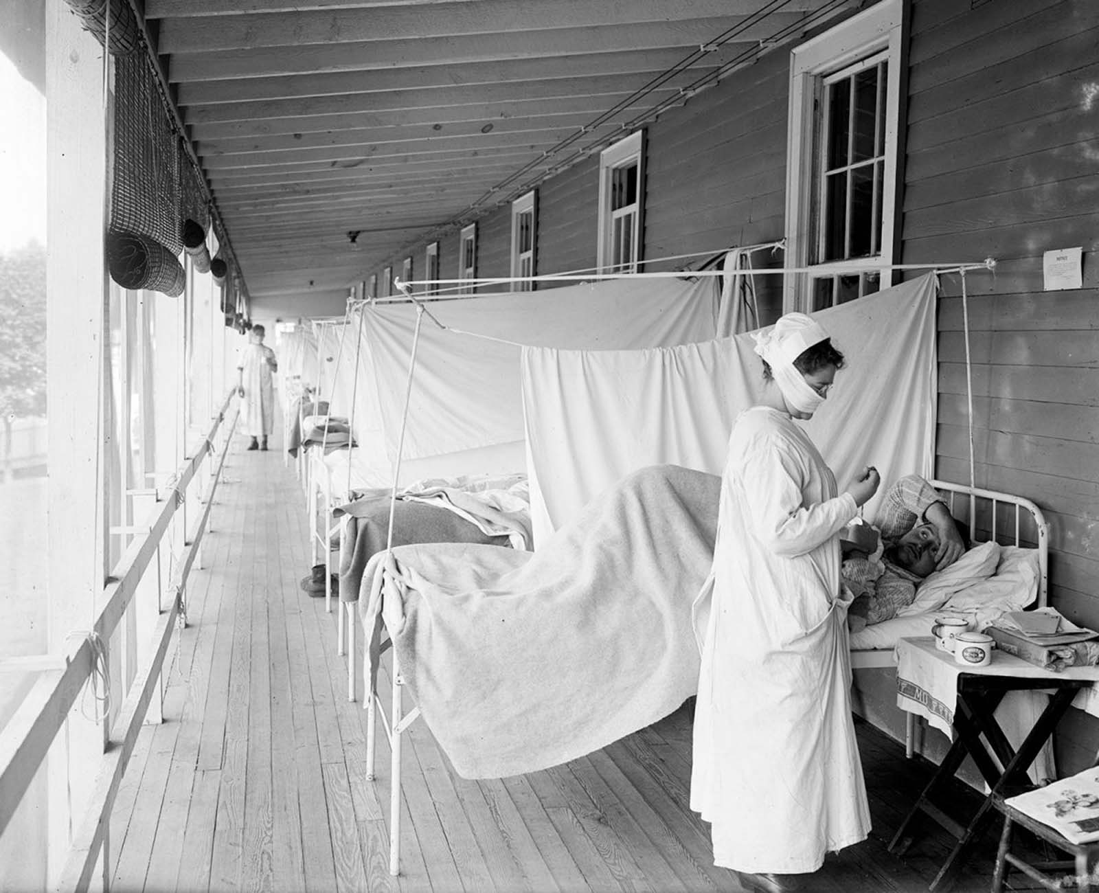 In this November 1918 photo, a nurse takes the pulse of a patient in the influenza ward of the Walter Reed hospital in Washington, D.C.
