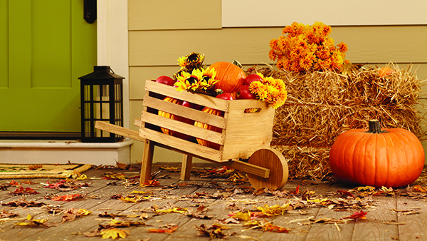 front porch decorated for Fall with wooden wheelbarrow