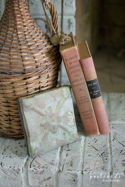 vintage books, ceiling tile plaque, and wicker demijohn on painted brick fireplace hearth