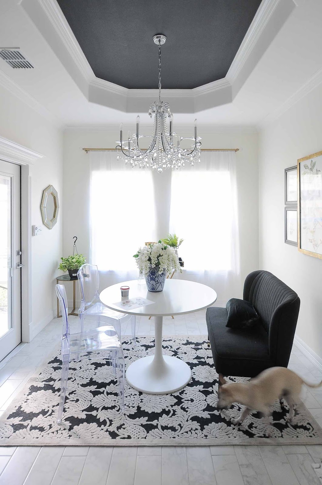 Arranging a functional layout in a small dining space. Love the round table, black ceiling and botanical vibe.