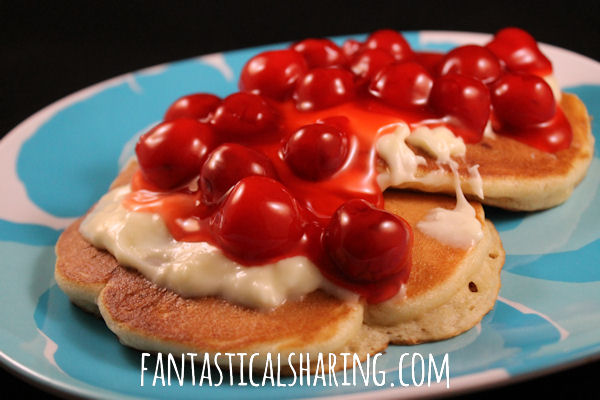 Cherry Cheesecake Pancakes | Fluffy pancakes w/pieces of cheesecake inside topped w/a cream cheese frosting & more than one cherry on top!