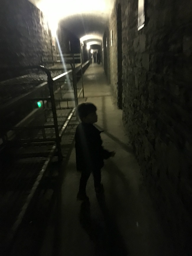 a-toddler-explores-cardiff-castle-world-war-two-shelters-view-of-inside-castle-tunnel-with-toddler-walking-down-dark-tunnel