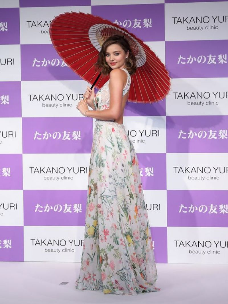 Miranda Kerr looks radiant while posing under a Japanese umbrella in a full-length floral frock at beauty event in Tokyo
