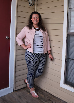 a woman wearing a striped tee, polka dot pants, a denim jacket, a statement necklace, and sandals