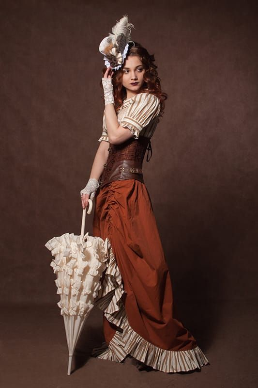 A woman wearing steampunk clothes in shades of orange, rust, brown and cream.