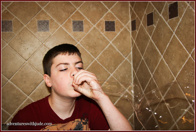 middle school child blowing bubbles with his hand instead of a bubble wand