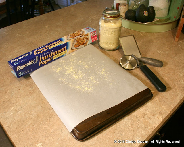 Baking sheet turned upside down, parchment paper cut to fit, and a sprinkle of cornmeal on the parchment paper.  Preparing to bake pizza in oven.