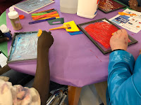 arms and hands shown working on paintings, using paint tools at a table with glue, paint, and tools in the center
