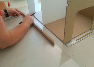 Person measuring and marking a piece of perspex against a beam.