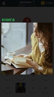 Около окна сидит девушка и читает книгу, перелистывая страницы