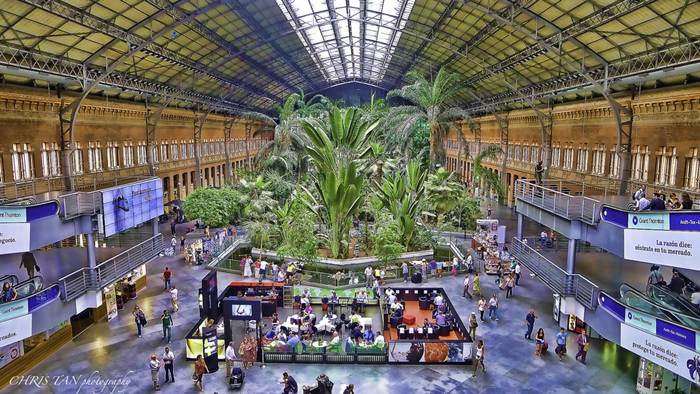 Madrid Atocha (Spanish: Estación de Madrid Atocha, also named Madrid Puerta de Atocha) is the largest railway station in Madrid. It is the primary station serving commuter trains (Cercanías), intercity and regional trains from the south, and the AVE high speed trains from Barcelona (Catalonia), Saragosse (Aragon), Seville (Andalusia) and Valencia (Levante Region). These train services are run by the Spanish national rail company, Renfe. The station is in the Atocha neighborhood of the district of Arganzuela. The original façade faces the Plaza del Emperador Carlos V, a site at which a variety of streets converge, including the Calle de Atocha, Paseo del Prado, Paseo de la Infanta Isabel, Avenida de la Ciudad de Barcelona, Calle de Méndez Álvaro, Paseo de las Delicias, Paseo de Santa María de la Cabeza, and Ronda de Atocha.
