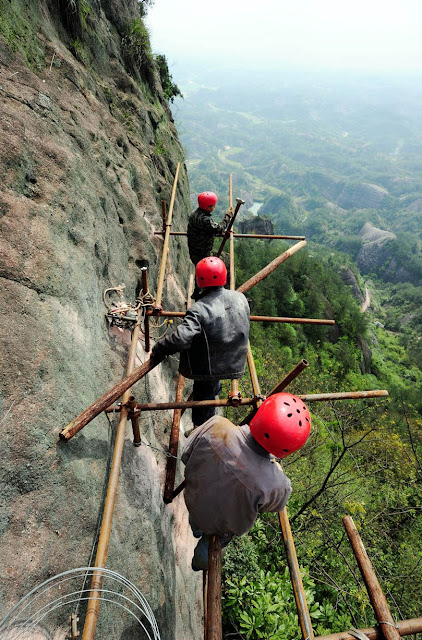 Workers stretch a long hose to pave a road on the cliff of a mountain