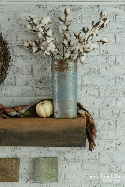 old metal sap bucket with faux cotton stems on wood fireplace mantel