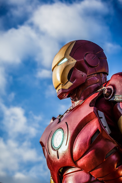 Iron Man, against a blue sky with clouds