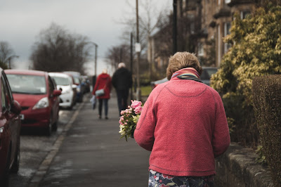 Elderly lady walking down the street, carrying flowers.
