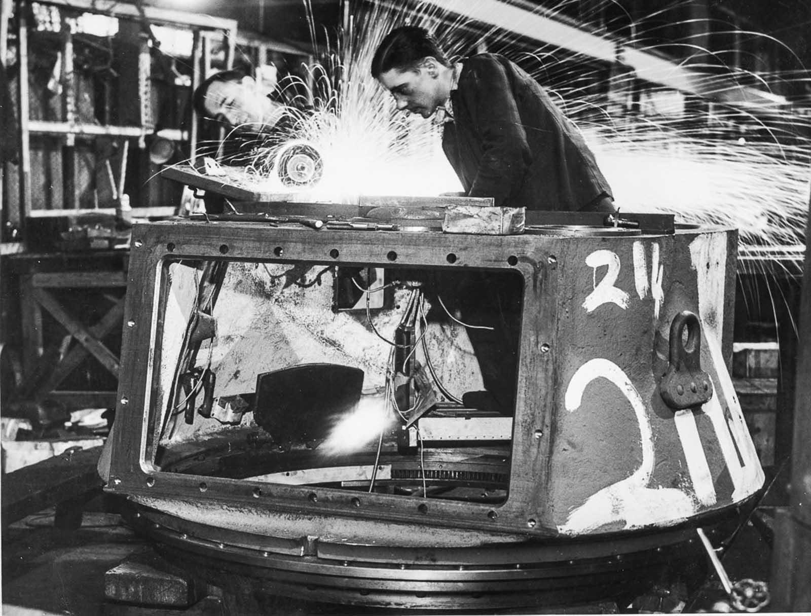 Trabajadores en una fábrica del Ministerio de Suministros haciendo una torreta para un