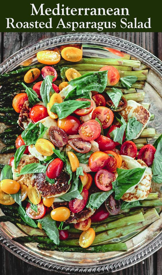 BEST roasted asparagus salad with tomatoes, basil, and a lightly sherry vinaigrette! Make this show-stopping dish #vegan or add halloumi or Greek feta for a twist! Grab recipe and tips on themediterraneandish.com #asparagus #roastedasparagus #mediterraneanfood #mediterraneanrecipes #mediterraneandiet #glutenfree