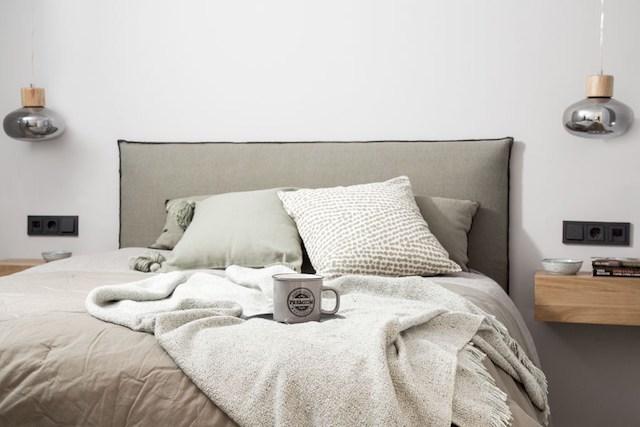 Dormitorio con mesitas voladas y lámparas colgantes