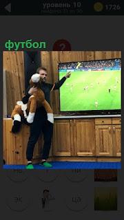 Мужчина с игрушкой около телевизора, по которому показывают футбол