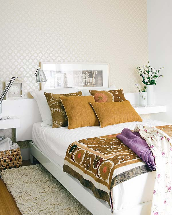 Bedroom in a tiny apartment with one wall covered in wallpaper, wood floor, a shag rug, white floating nightstands on which holds a silver lamp the other a flower arrangement, the bed has sienna colored pillows and a matching patterned throw