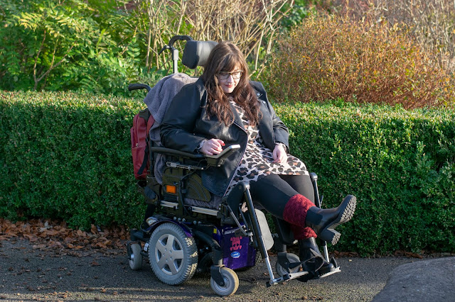 Woman sat in powerchair in leopard print dress and leather jacket. One leg in the air and looking at boot. Greenery in background
