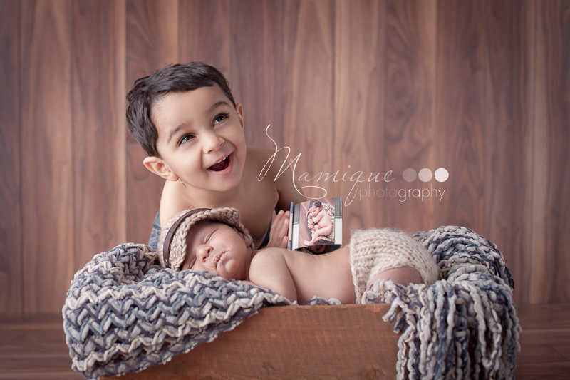 Big brother showing of his own newborn photos to baby brother