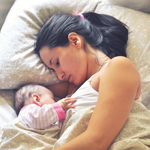 Mère avec son bébé dans le lit