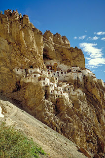 Cluster of whitewashed dwellings all connected on the ledge of a mountain