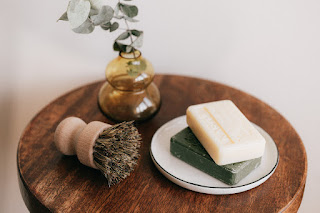 Soap, vase and brush on wooden round table