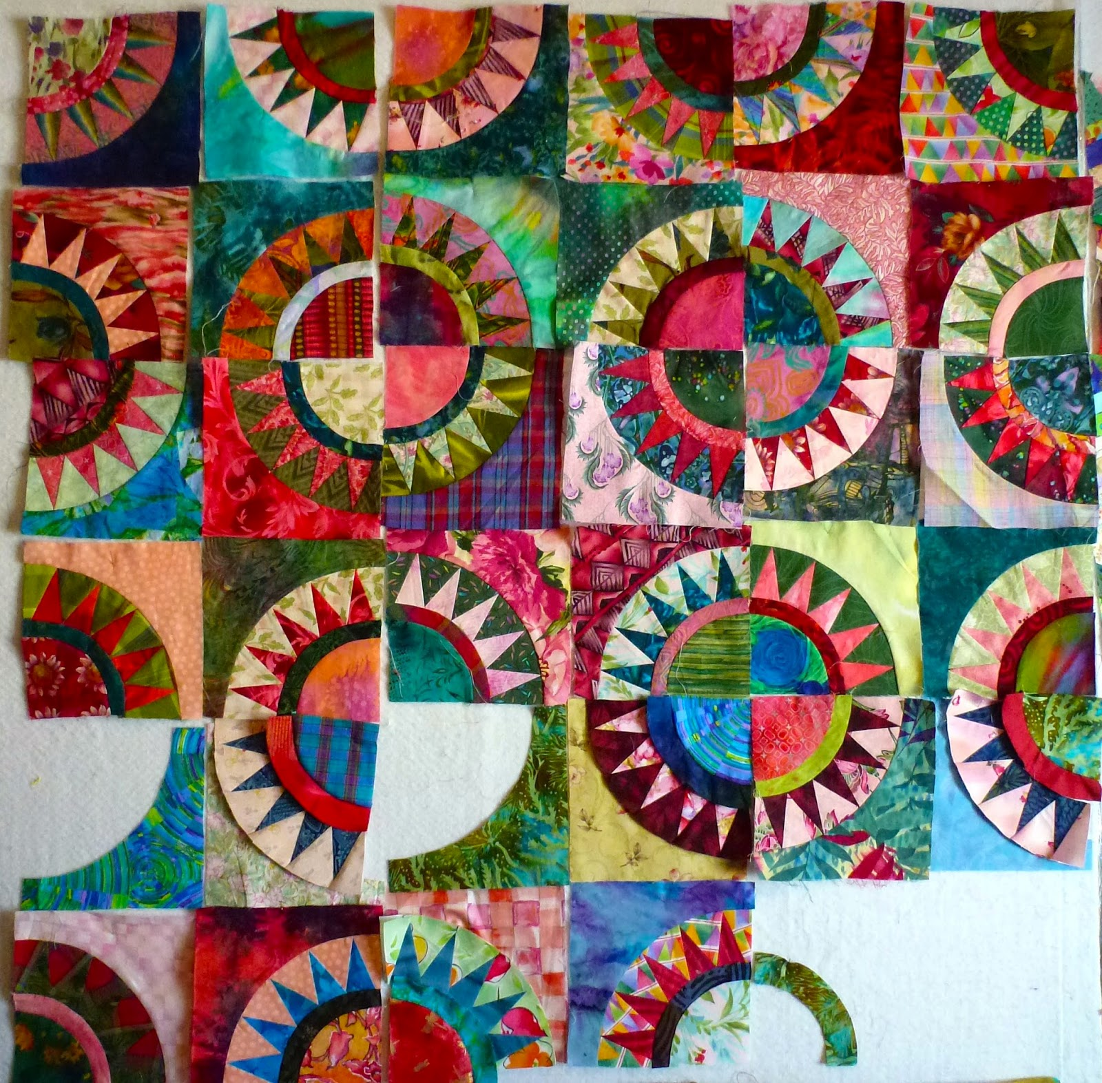 Red, pink, green and blue quilt blocks with quarter circles and five teeth.