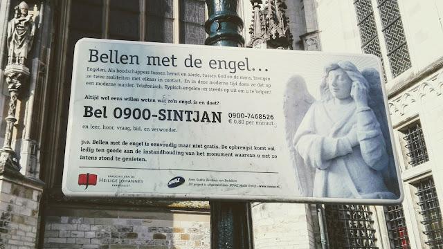 Bord dat staat bij de Sint Janskathedraal in Den Bosch: Bellen met de engel..., met een telefoonnummer erbijl.