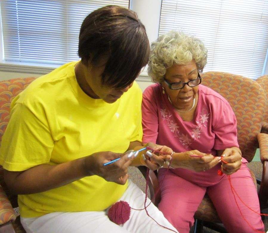 Joan Black teaching student how to crochet