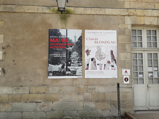Posters advertising exhibitions on wall of the chateau at Tours