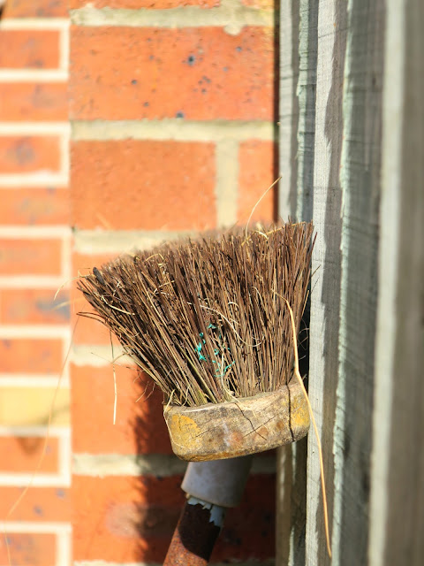 Head of a broom leaning against a wooden fence by a brick wall