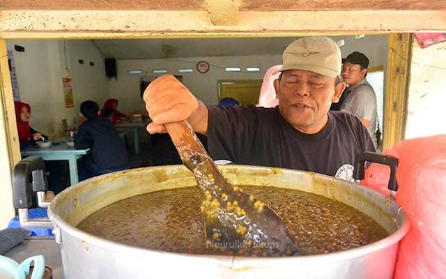 Pak Mudhori mengaduk bubur kacang ijo di dalam kuali
