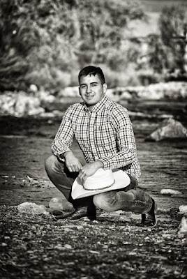 a young man crouches on a river bank for his senior portraits