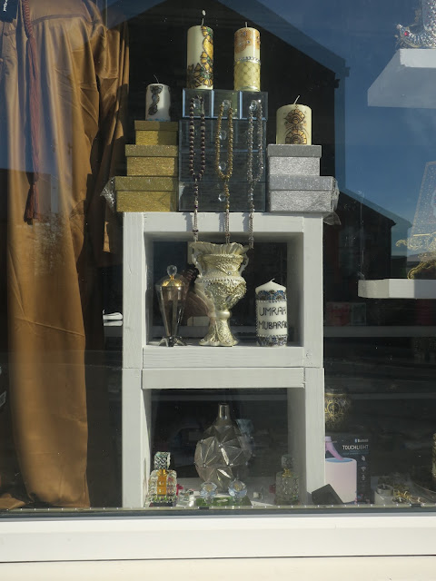 Gold material, candles and boxes in shop window display