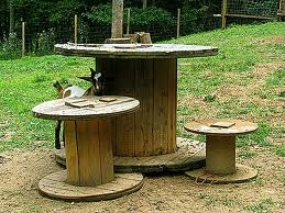 Large wooden spools turned on their sides so that there is a circular top and bottom with a narrower cylinder connecting them