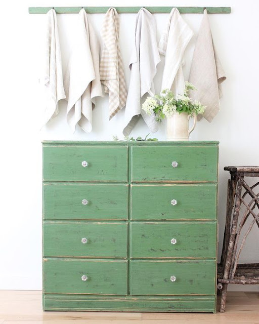 old chest of drawers painted green with glass knobs