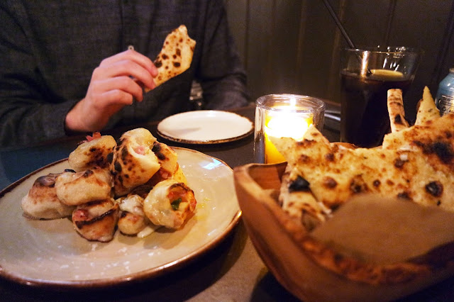 a plate with a pile of dough rolls, and a wooden basket containing pieces of garlic bread