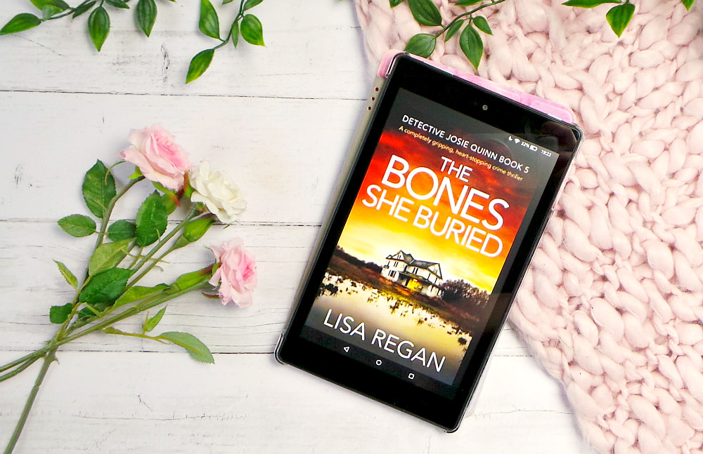 A kindle fire is pictured on a white wooden backdrop next to some roses with a chunky knit pink blanket. The cover forThe bones she buried is shown on the screen.